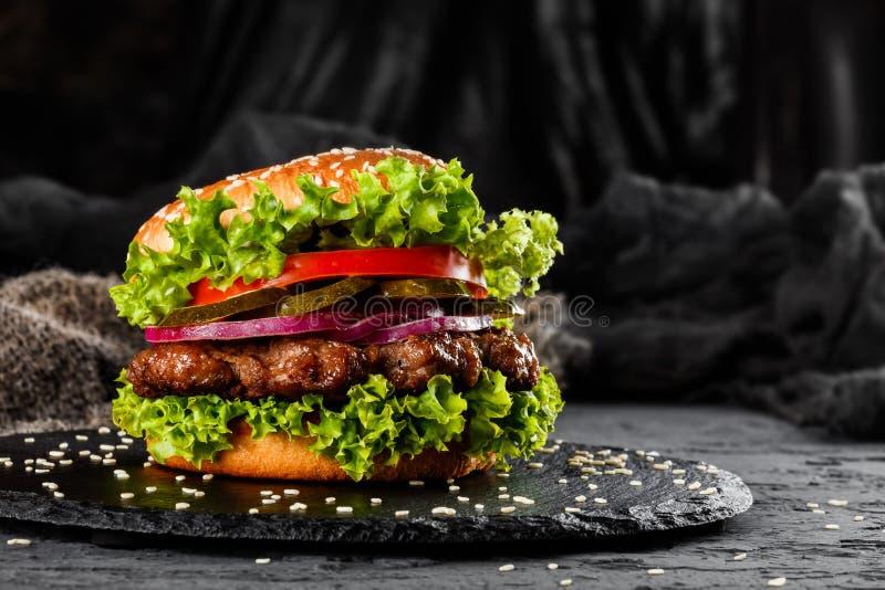 Жалуйтесь бургер с томатами, красными луками, огурцом и салатом на черном шифере над темной предпосылкой стоковые фотографии rf