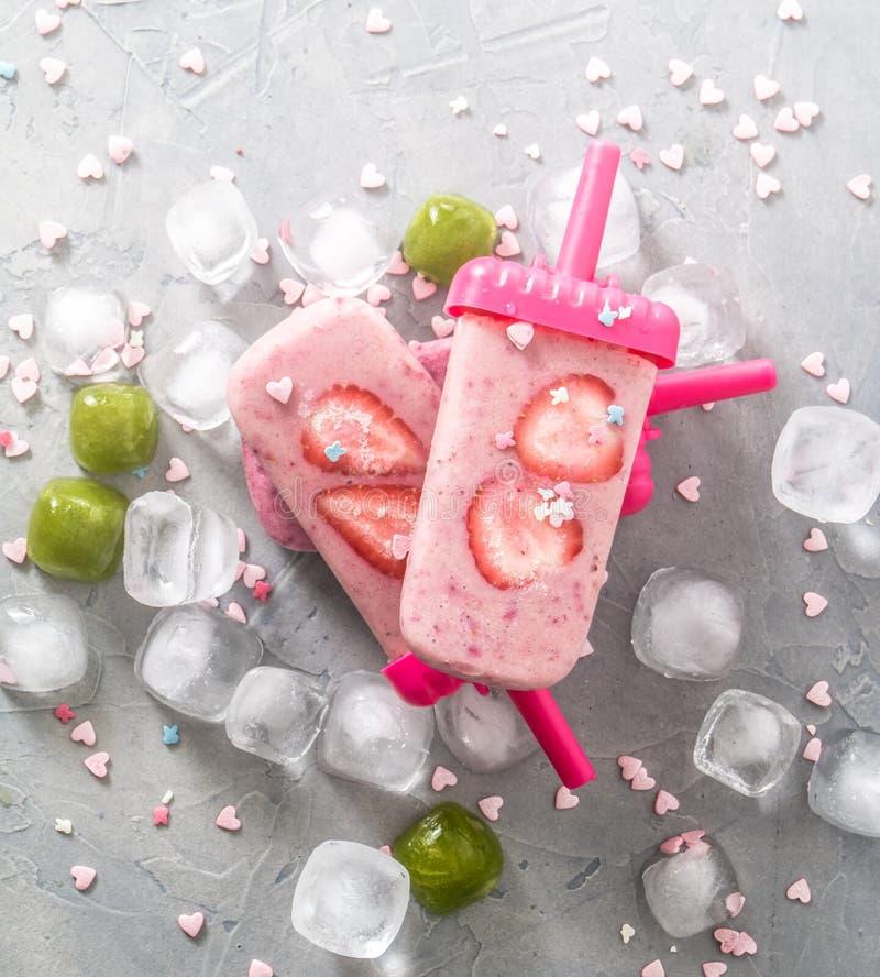 Жара лета: освежая розовый лед плодоовощ при части клубники окруженные прозрачными и зелеными кубами льда на серой таблице стоковые фото