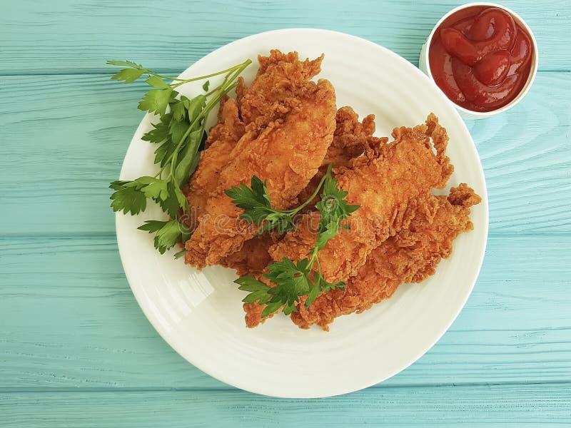 Жареная курица зажарила очень вкусный обедающий в обваливать в сухарях, петрушку обеда, кетчуп на голубое деревянном стоковые фото