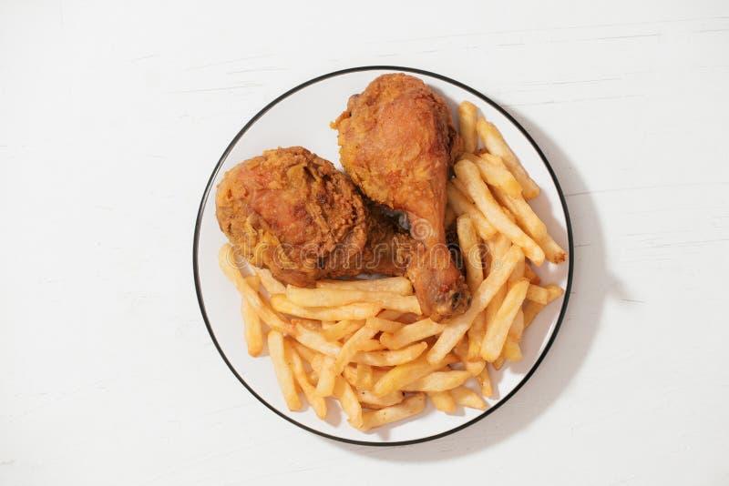 Жареная курица и французский картофель фри в белой плите изолированной на белой предпосылке стоковые изображения