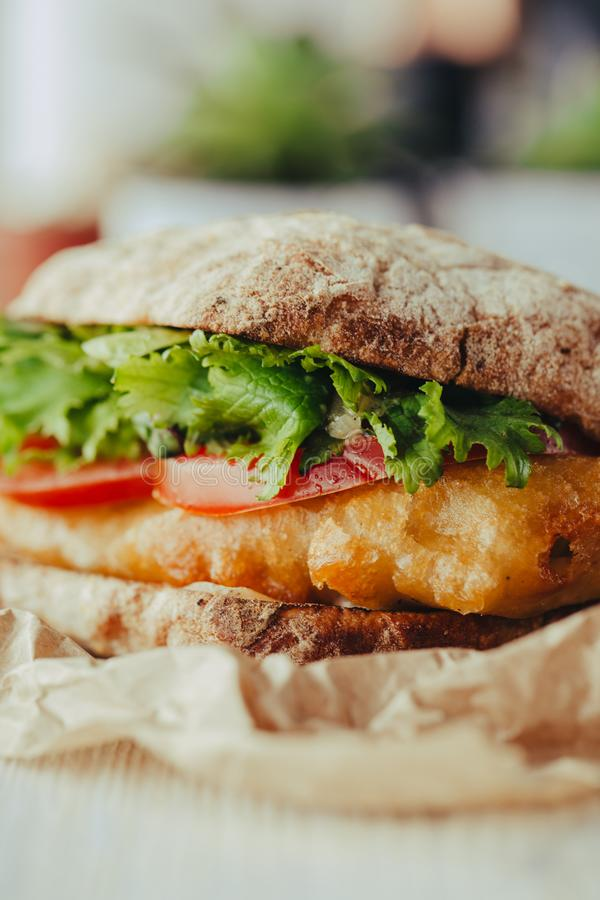 Fried fish Sandwich with lettuce, tomato with tartar sauce. author`s recipe street food stock images
