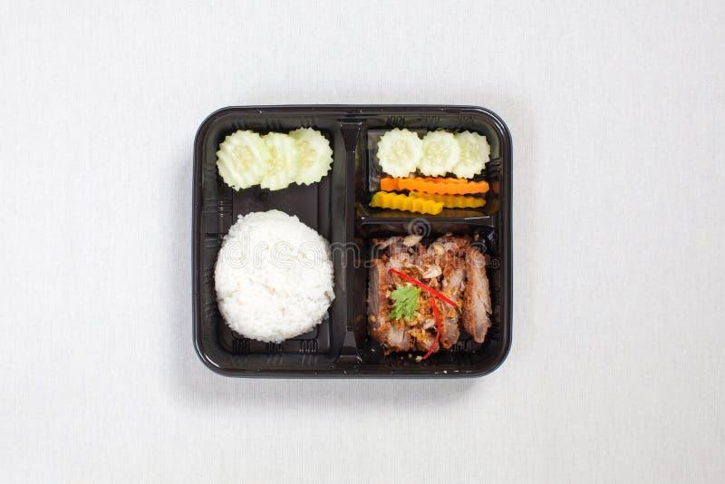 Жареная свинина с чесноком, перцем и рисом, помещенными в черную пластиковую коробку, положить на белую скатерть, коробку с едой стоковые изображения
