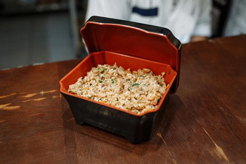 Жареные рисы с овощами в черной прямоугольной коробке с красной кишкой на предпосылке деревянного стола стоковое фото