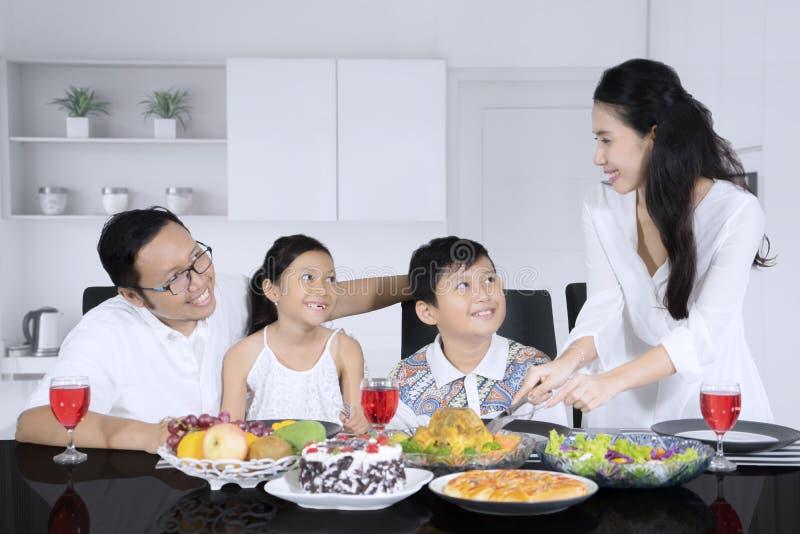 Жареный цыпленок сервировки молодой женщины для ее семьи стоковое фото rf