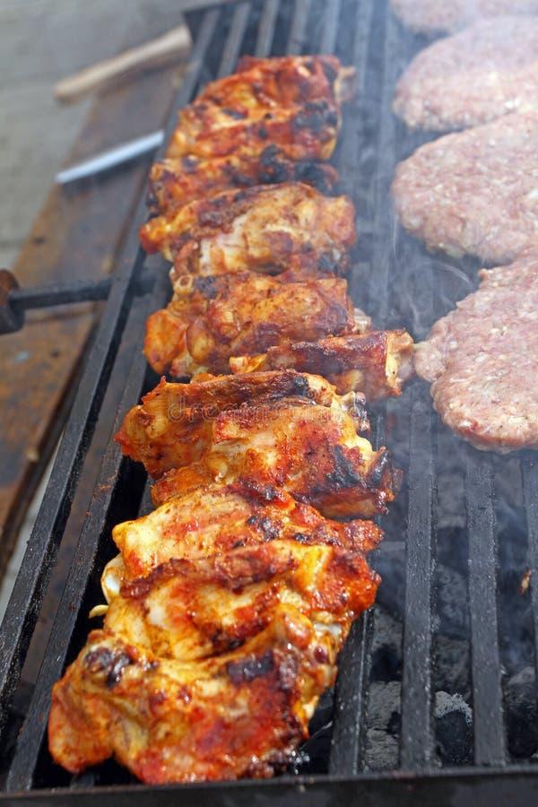 Жарить сосиски, бургеры, стейк свинины на гриле газа барбекю для партии Хот-доги, сосиски и гамбургеры на барбекю, bbq Smok стоковое изображение