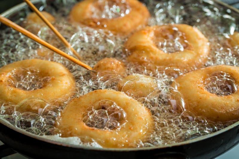 Жарить сладостные и вкусные donuts на свежем масле стоковая фотография