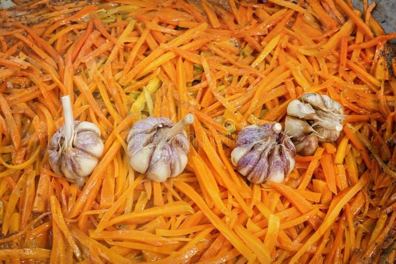 Жарят в духовке в большой сковороде на улице для того чтобы подготовить морковей и чеснок традиционное азиатское блюдо pilaf стоковое изображение rf