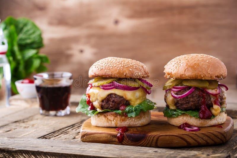 Жалуйтесь бургеры с корнишонами, красным луком и салатом стоковые фото
