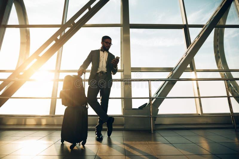Ждать полет Бизнесмен с багажем в крупном аэропорте стоковые изображения