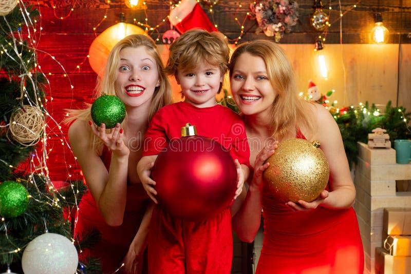 Желания утехи мира любов Мальчик ребенк с сестрами мамы или тетушек имея потеху Потеха семьи рождества Рождественская вечеринка К стоковое фото