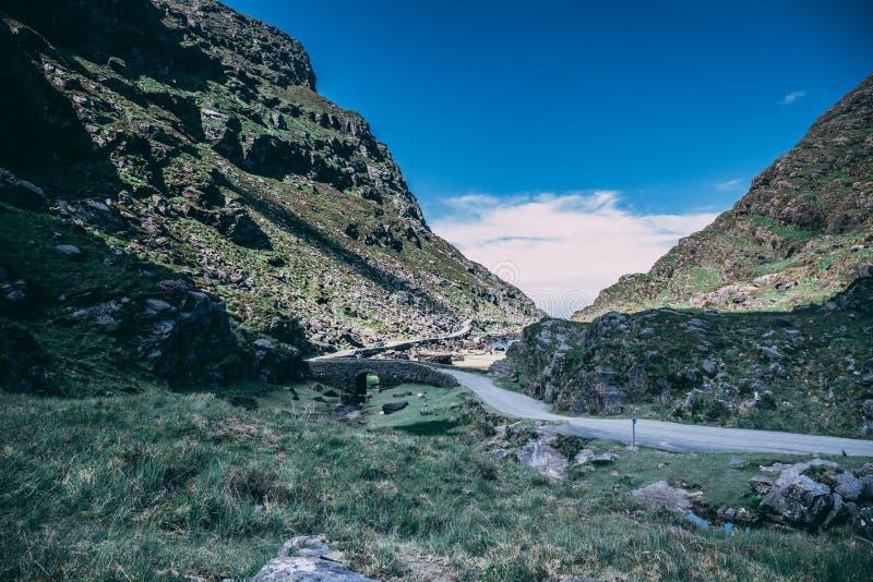Желающ мост зазора Dunloe, узкого перевала выкованного между сильными запахами MacGillycuddy и фиолетовой горой стоковые фото
