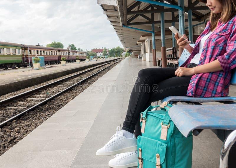 Железная дорога путешественника и рюкзака молодой женщины ждать на вокзале, молодой женщине сидя с использованием smartphone на в стоковые фотографии rf