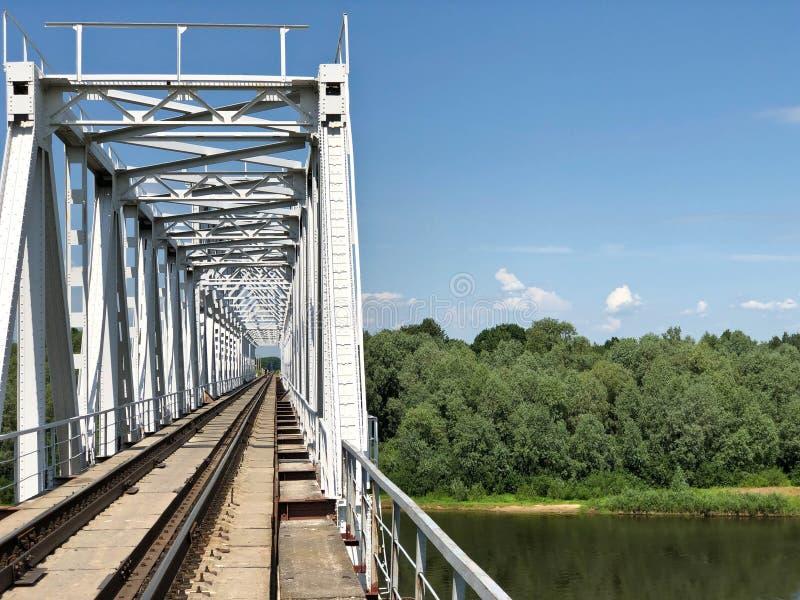 Железнодорожный мост над рекой против голубого неба стоковые изображения