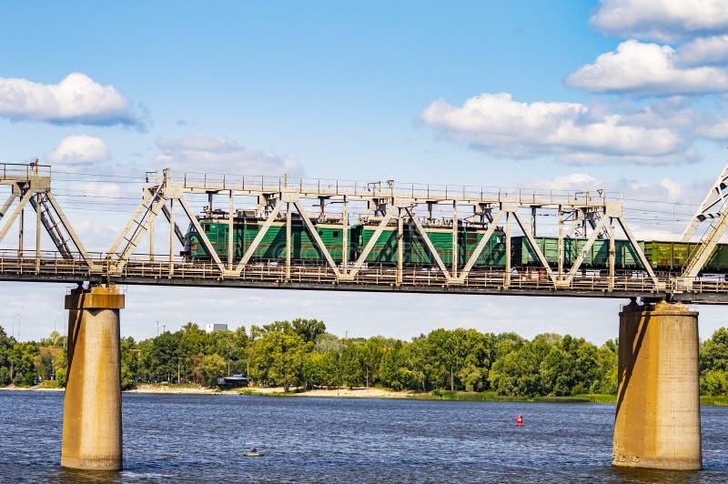 Железнодорожный мост над рекой с поездом против голубого неба стоковая фотография