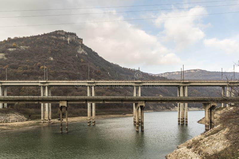Железнодорожный мост с поездами пропуская над запрудой Tsonevo стоковое изображение