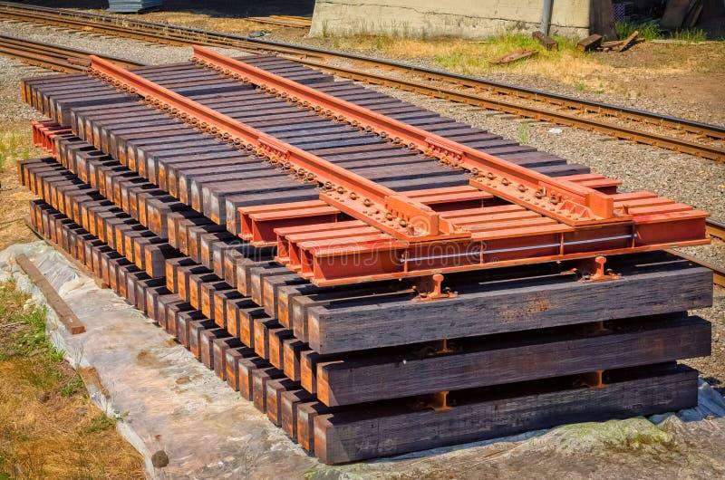 Железнодорожный путь распределяет штабелированное готовое для того чтобы стать частью железнодорожного ремонта стоковая фотография rf