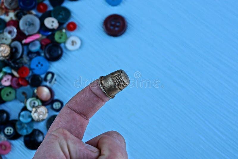 Железное кольцо на пальце на фоне покрашенных кнопок на таблице стоковые изображения