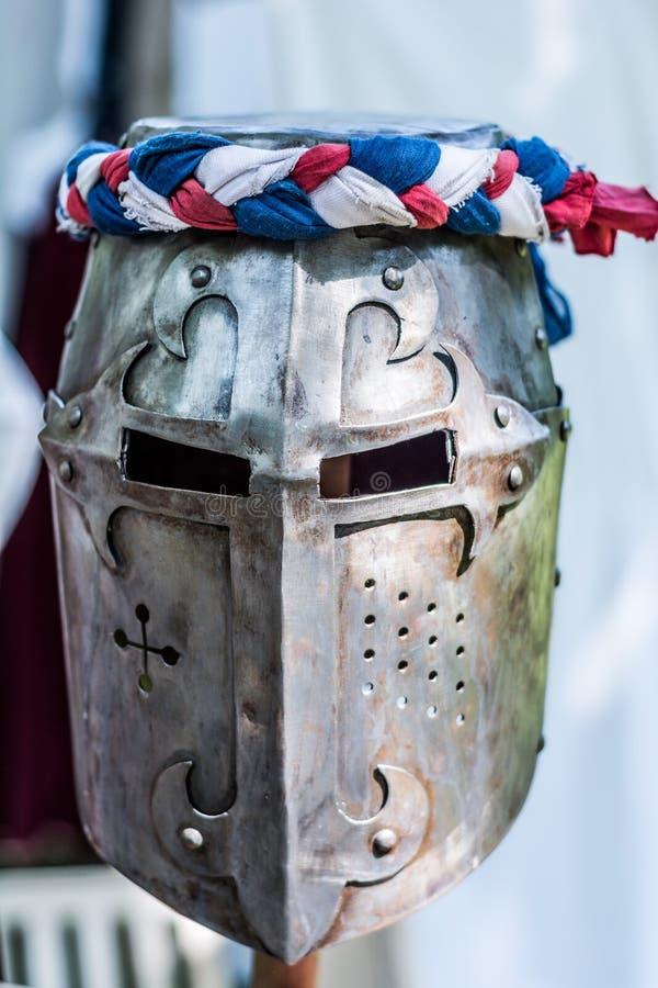 Железный шлем средневекового рыцаря на деревянной стойке стоковые изображения