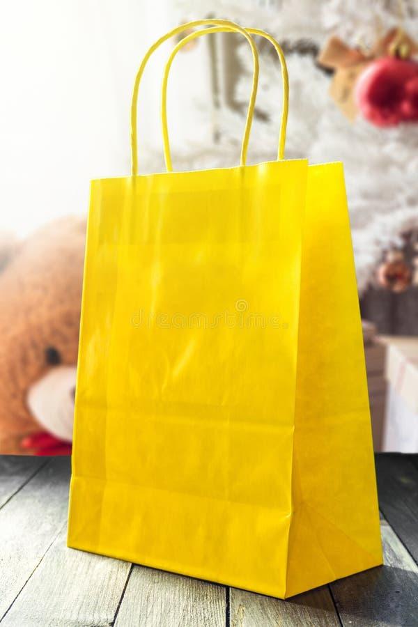 Желтая бумажная сумка против рождественской елки стоковая фотография