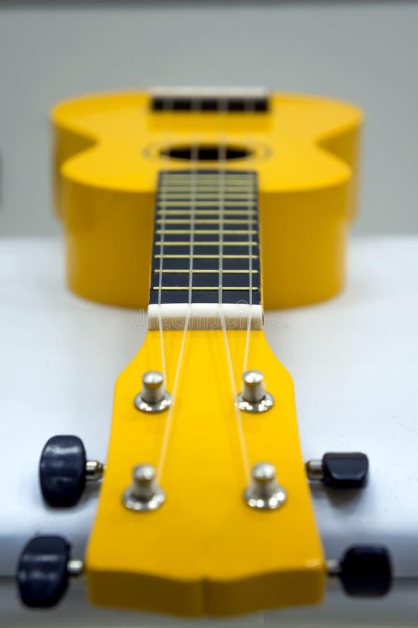 Желтая гавайская гитара, мягкий фокус на белой предпосылке стоковое изображение rf