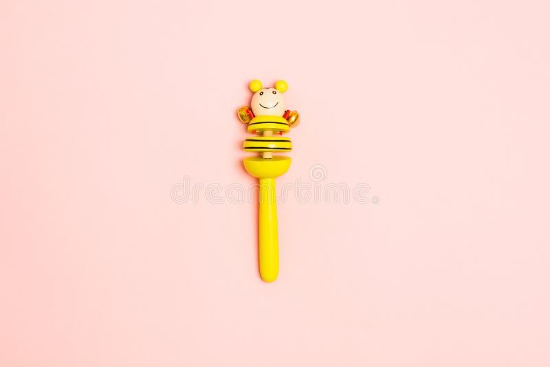 Желтая деревянная трещотка младенца с колоколами над розовой предпосылкой r r r стоковая фотография rf
