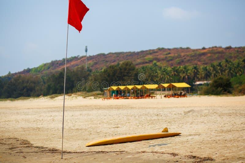 Желтая доска спасителя для серфинга лежит на песке используемом личной охраной работая на пляже Arambol стоковая фотография rf