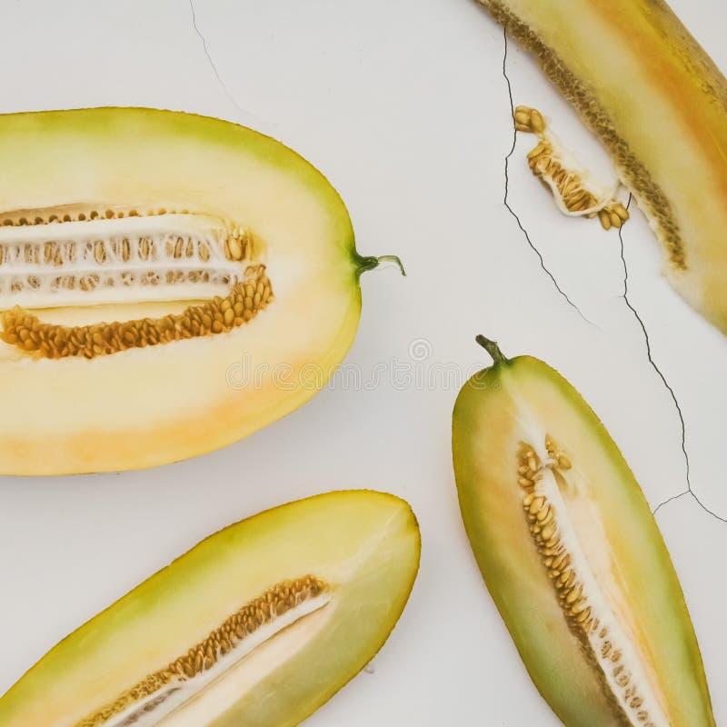Желтая зрелая сладкая дыня с семенами, отрезок в части, на белом треснутом на заднем плане стоковая фотография rf