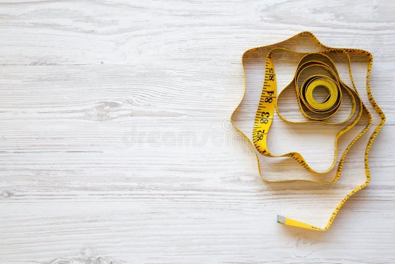 Желтая измеряя лента на белом деревянном столе, взгляд сверху стоковая фотография rf