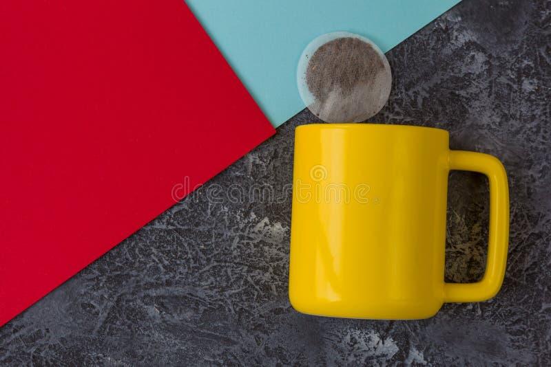 Желтая кружка на черной каменной предпосылке Бумага пакетика чая, печений, красных и голубых r стоковые изображения