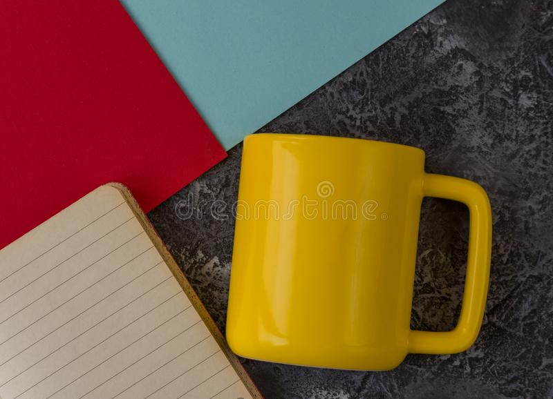 Желтая кружка с тетрадью на темной каменной предпосылке Голубая и красная бумага r стоковое изображение rf