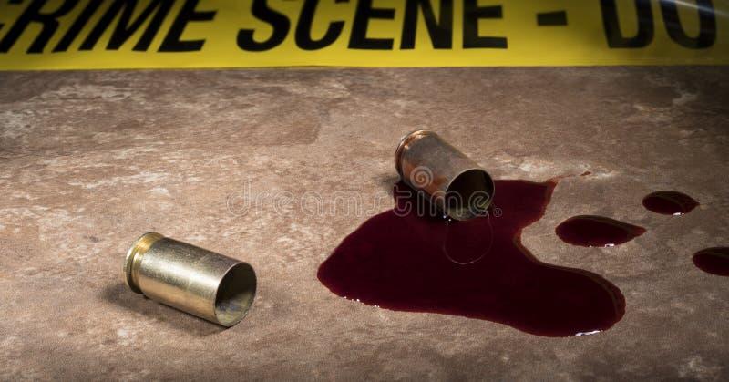 Желтая лента места преступления за 2 раковинами и кровями пистолета стоковая фотография