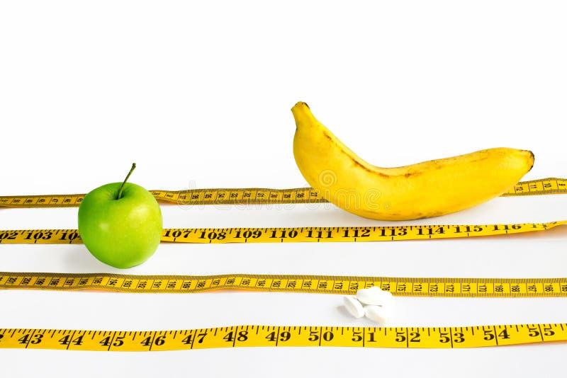 Желтая лента сантиметра клала вне как следы спорт на которых состязаются зеленые Яблоко, корки и банан изолированное на белой пре стоковое фото