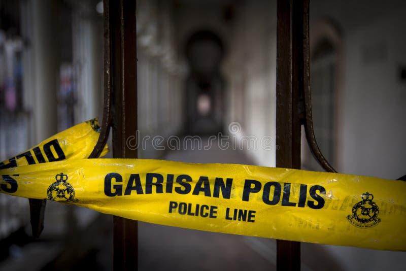 Желтая лента с wordings линии полиции не пересекает и в язык английских и малайца стоковые фото