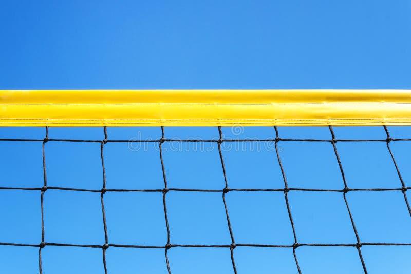 желтая покрашенная сеть волейбола или тенниса пляжа предпосылки шарика игр лета против голубого неба для спортивных мероприятий C стоковое фото rf