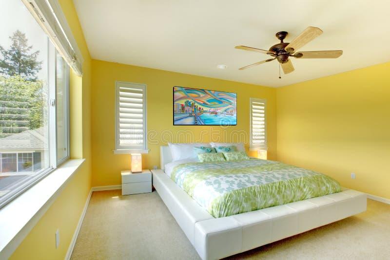 Желтая самомоднейшая спальня с белой кроватью. стоковое изображение