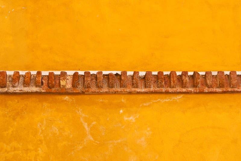 Желтая стена самана с уравновешиванием кирпича стоковое фото rf