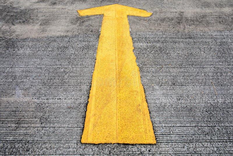 Желтая стрелка на конкретной земле улицы или дороги автостоянки стоковое фото rf