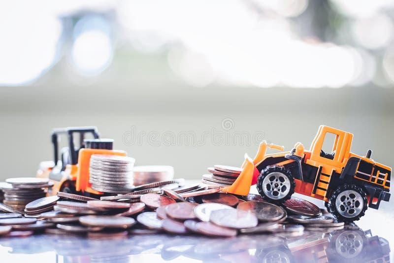 Желтая тяжелая техника игрушки с кучей монеток стоковые изображения rf