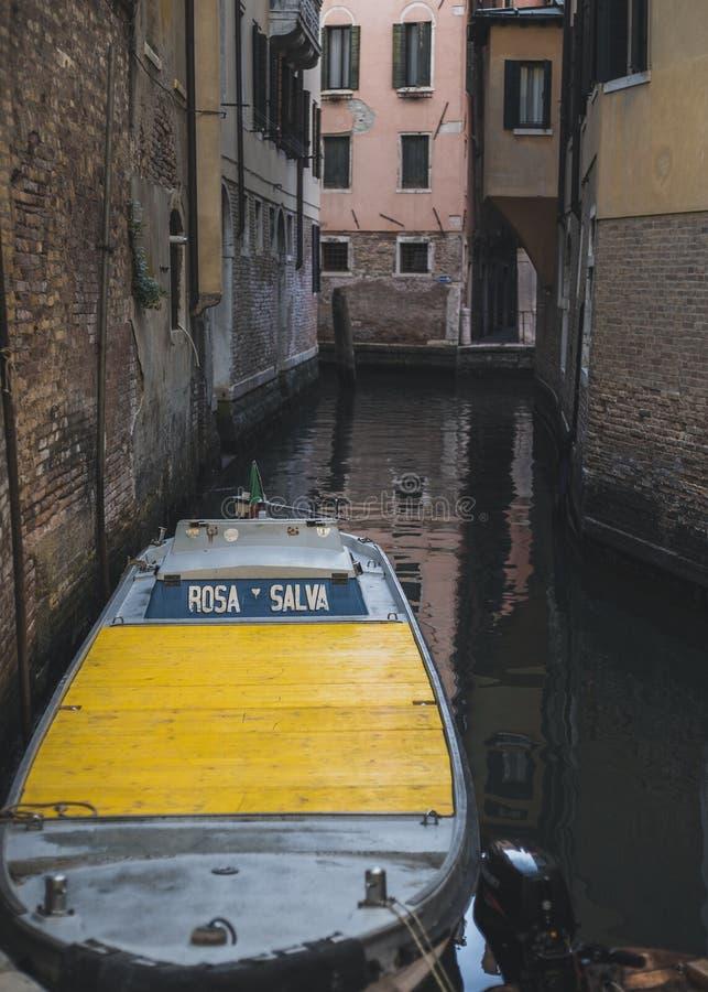 Желтая шлюпка на венецианском канале стоковое изображение rf