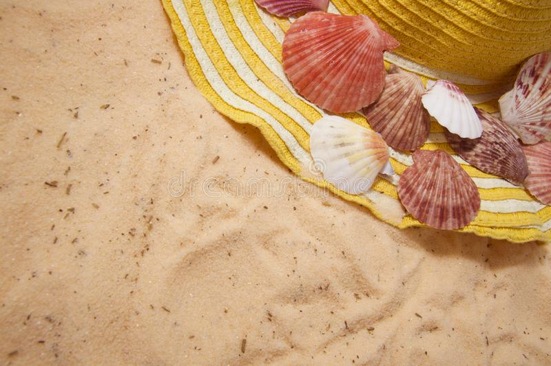 Желтая шляпа с раковинами лежа на золотом песке стоковая фотография
