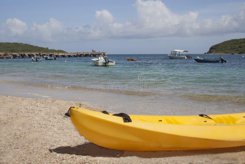 Желтое каноэ отдыхает на пляже стоковые фотографии rf