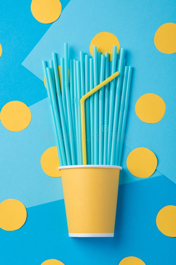 Желтые и голубые соломы для партии в бумажных стаканчиках на ярком bac стоковое фото
