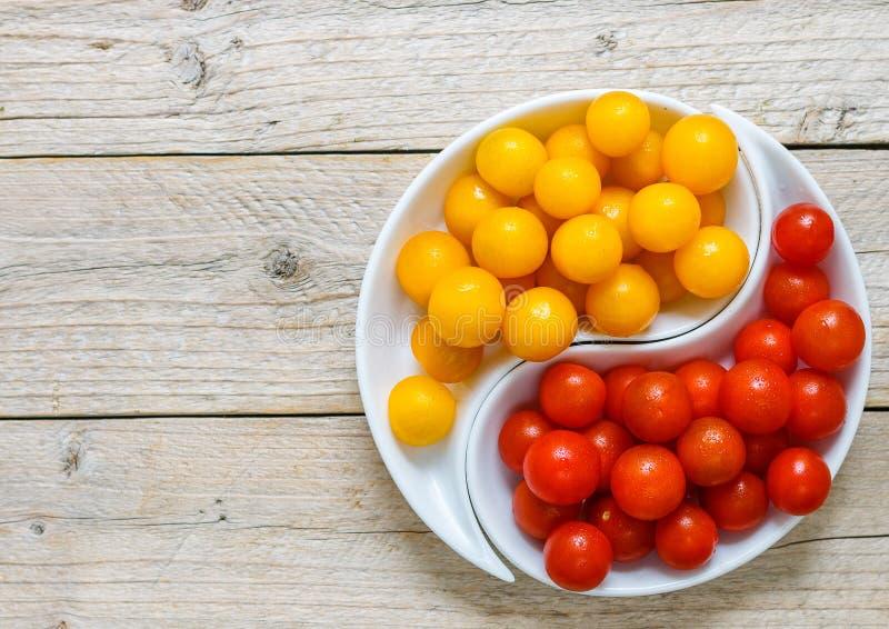 Желтые и красные томаты вишни с водой падают свежее сочное стоковые изображения rf