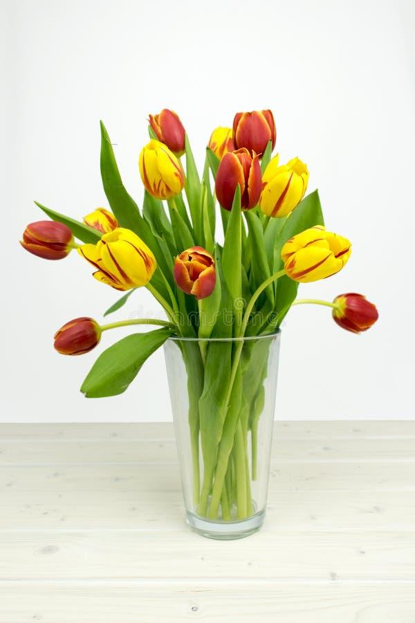 Желтые и красные тюльпаны на деревянном столе стоковая фотография