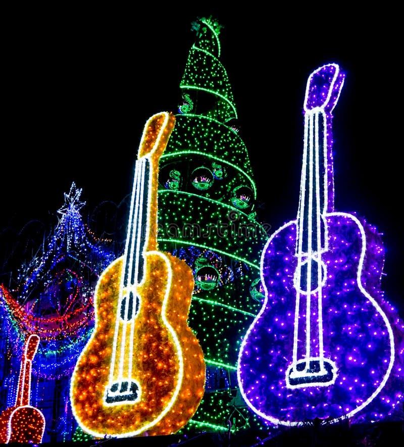 Желтые и фиолетовые гитары и дерево и орнаменты праздника освещенные вверх стоковое фото rf
