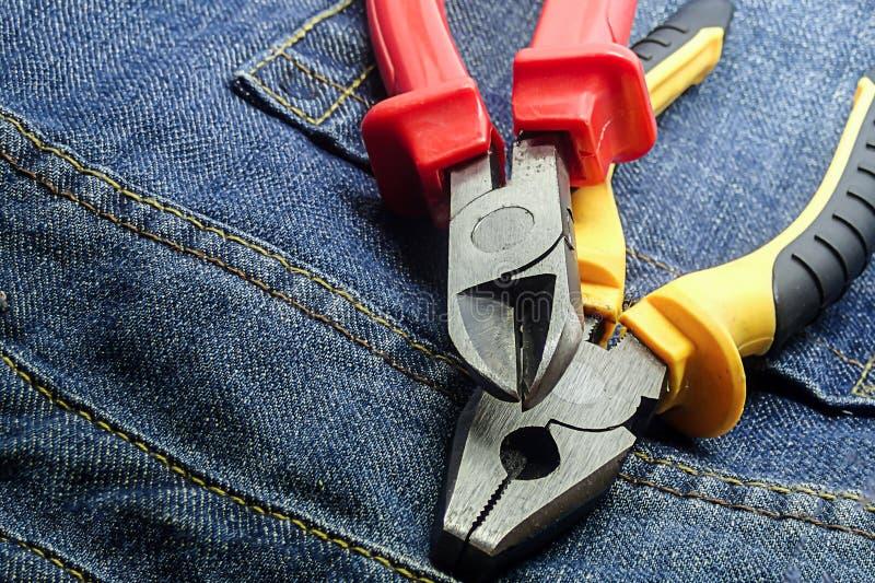Желтые красные острозубцы на плоскогубцах пары стиля grunge инструмента деятельности предпосылки джинсов конструируют основание стоковые изображения rf
