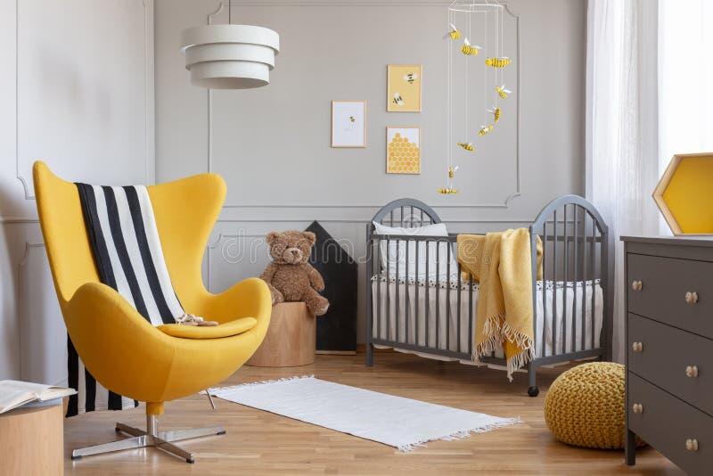 Желтые кресло, плюшевый мишка и шпаргалка в современном интерьере комнаты ребенк стоковые изображения