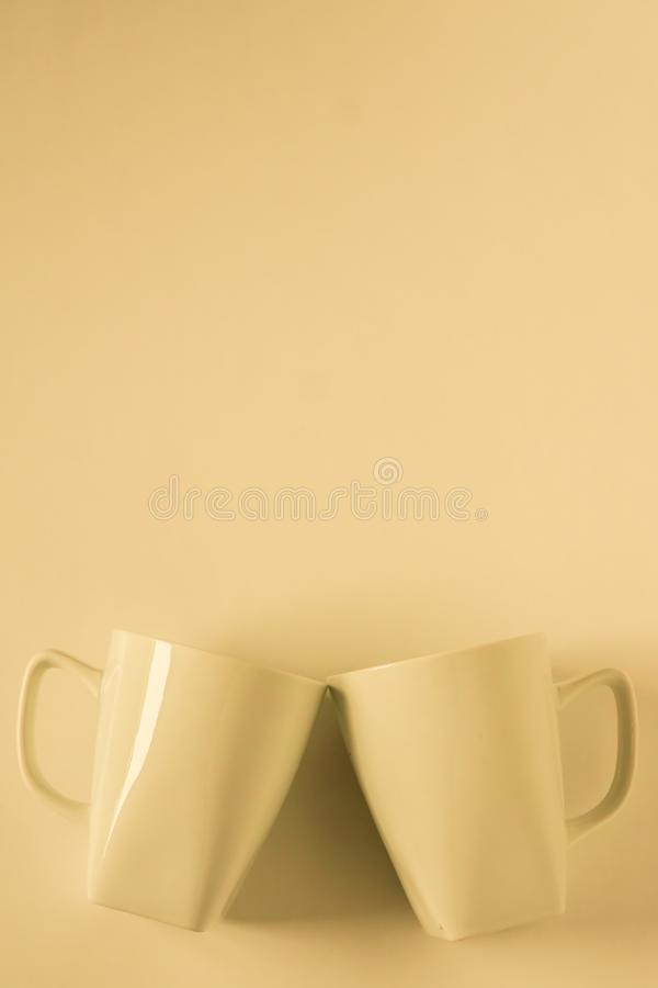 Желтые кружки кофе на желтой предпосылке clinking в приветственных восклицаниях с пустым космосом экземпляра стоковое изображение rf