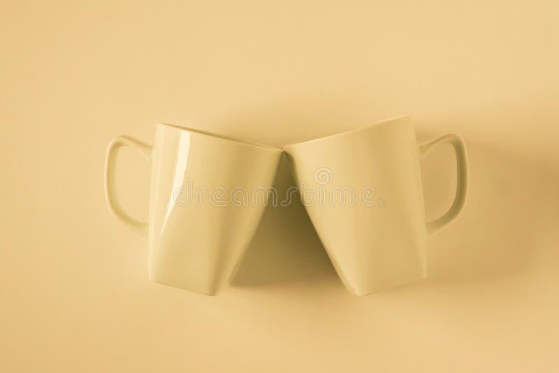 Желтые кружки кофе на желтой предпосылке clinking в приветственных восклицаниях с пустым космосом экземпляра стоковая фотография rf