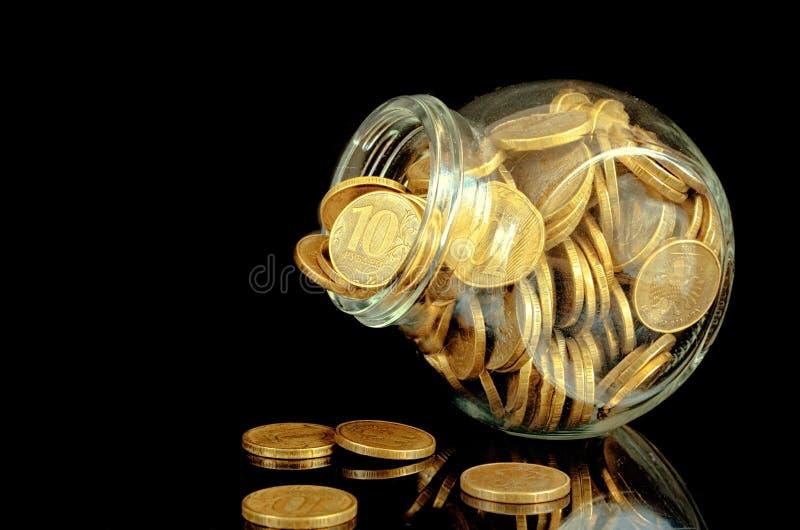 Желтые монетки в стеклянном опарнике на черной предпосылке с отражением стоковые изображения rf